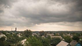 Stormmoln i himlen som flyttar sig över husen i staden arkivfilmer