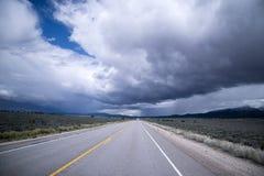 Stormmoln och ändlös staightväg i Nevada Arkivfoton