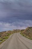 Stormmoln och grusväg i sydliga Utah Arkivbilder