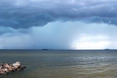 Stormmoln, regn och blixt över havet royaltyfria bilder