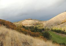 Stormmoln samlar över en färgrik höstbacke med det gröna fältet i dalen Fotografering för Bildbyråer