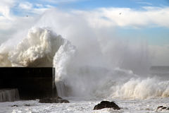 Storms. Sea storm with waves crashing against the pier at the mouth of the Douro River on a sunny day Royalty Free Stock Photos