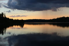Storms in the Distance. Sunset over the water with a storm looming in the distance Royalty Free Stock Photo