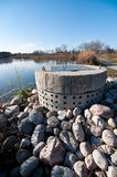 Stormwater Management - Perforated Concrete Pipe. A perforated concrete pipe forms part of a stormwater management system in a suburban pond Royalty Free Stock Image