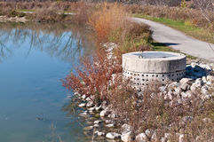 Stormwater Management System - Concrete Pipe. A perforated concrete pipe forms part of a stormwater management system in a suburban pond Royalty Free Stock Photography