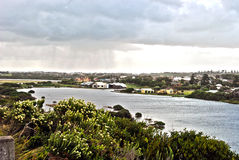 Stormy afternoon. Low clouds dominating a township on a waterway Royalty Free Stock Image