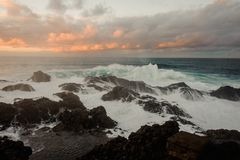 Stormy azure sea and a lot of rocks under the cloudy sky. During sunset on summer evening royalty free stock images