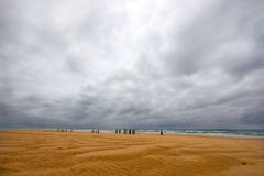 Stormy beach and women. Beach with stormy skies and indigenous fishermen wives waiting for the fishing dhows to come in with the catch of the day royalty free stock photo
