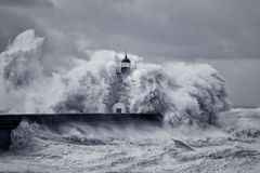 Stormy big waves. Old river Douro mouth lighthouse embrassed by huge sea waves and devastated by strong winds. Converted black and white and toned blue royalty free stock images