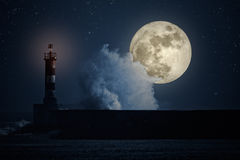 Stormy breaking wave at night. Big stormy wave breaking over pier and beacon in a full moon night. Photo composition royalty free stock photography