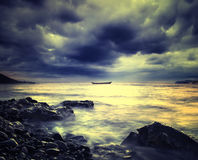 Stormy clouds. Sea and rock at the sunset Stock Images