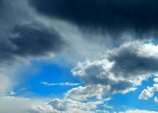 Stormy clouds in the blue sky with the dawn of the sun rays Stock Photography