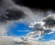 Stormy clouds in the blue sky with the dawn of the sun rays Royalty Free Stock Images