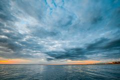 Stormy clouds over calm ocean water. Stormy clouds over calm ocean water at sunset seascape Stock Images