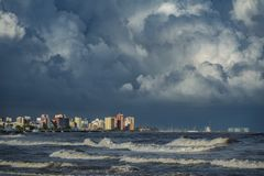 Stormy clouds over coastal buildings with sea. Long shot of stormy clouds over coastal city buildings stock image