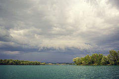 Stormy clouds over a green lake Royalty Free Stock Photography