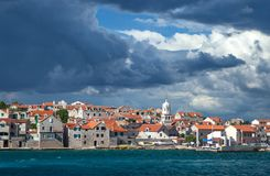 Stormy clouds over old village Šepurine on the island of Prvić. Stormy clouds above and choppy sea water surrounding old, stone built, village Šepurine royalty free stock images