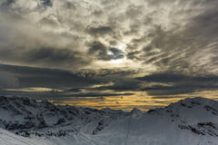 Stormy clouds over a snowcaped mountain range. With yellow sky Royalty Free Stock Photos