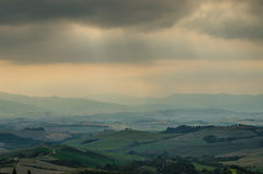 Stormy clouds over Tuscany's hills. With some rays of light peaking through Royalty Free Stock Photo