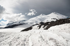 Stormy clouds overhang over the snow-capped mountain Elbrus Royalty Free Stock Images