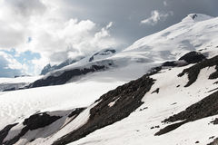 Stormy clouds overhang over the snow-capped mountain Elbrus Stock Image