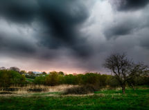 Stormy clouds under green landscape stock image