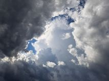 Stormy cloudscape with specs of blue sky. Sunrays beaming through dark stormy cumulus storm clouds Stock Photos