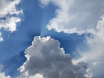 Stormy cloudscape with specs of blue sky. Sunrays beaming through dark stormy cumulus storm clouds Stock Image