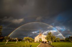 Stormy cloudy rainbow sky in countryside stock images
