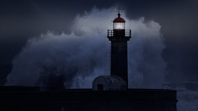 Stormy coast at night. Big stormy waves against lit lighthouse at night royalty free stock photo