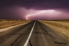 Stormy country road at night, with intense lightning strikes. Stock Photos