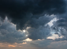 Stormy dark clouds. Heavy cumulus before storm over amber horizon Royalty Free Stock Photo