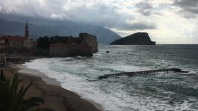 Stormy day in Budva. Budva, Montenegro - Richard`s beach on a stormy afternoon with waves smashing on the beach, old town with citadel in background stock video
