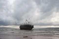 Stormy derelict. A derelict fishing boat surrounded by stormy clouds at Ettrick Bay, Bute stock photo