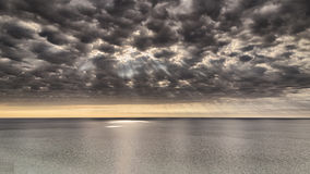 Stormy dramatic clouds and sun rays over a lake Stock Photos