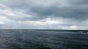 Stormy evening at the rough sea with overcast of heavy clouds and sunbeams