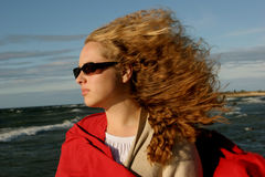 Stormy girl in sun glases. Girl on suny  windy day near the sea Stock Photography