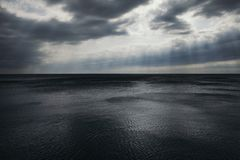 Stormy gray-blue sea and sky in the clouds and rays of the sun. Russia, the Black Sea Royalty Free Stock Photo