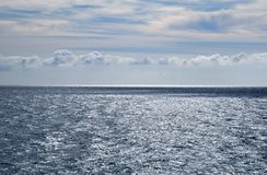 Stormy grey sea, calm before the storm, blue sky with some white. And grey clouds, seascape with a horizon line royalty free stock photos
