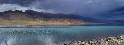 Stormy hurricane to the high mountains of lake: dark blue clouds descend to the top of the hills, along the azure surface of the l Stock Photos