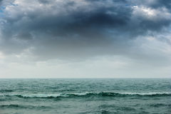 Stormy intense dark clouds over the ocean Stock Photos