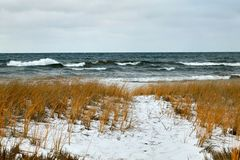Stormy lake and snow covered winter shoreline. Rough, stormy lake and snow covered winter shoreline with no people in Michigan Royalty Free Stock Images