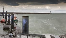 Stormy landscape in the entrance of the main harbor in low tide, Stock Image