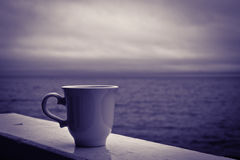 Stormy Morning Coffee. Cup of coffee on balcony railing overlooking the lake on a stormy morning royalty free stock photo