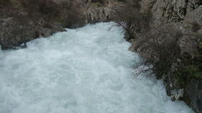 A stormy mountain river flows widely among the mountains. stock video footage