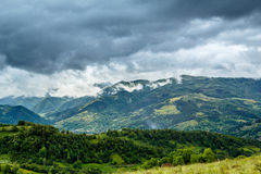 Stormy Mountains. View from the Bedeleu peak, a part of the Trascau Mountains, in a rainy day with dramatic clouds. The village from the valley is Salciua Royalty Free Stock Photo