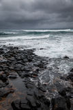 Stormy ocean , dramatic sky. Stormy weather pushes waves over a rocky volcanic shoreline in Hawaii Royalty Free Stock Photo