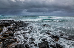 Stormy ocean , dramatic sky. Stormy weather pushes waves over a rocky volcanic shoreline in Hawaii Stock Photo