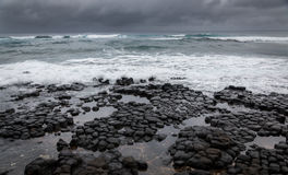 Stormy ocean , dramatic sky. Stormy weather pushes waves over a rocky volcanic shoreline in Hawaii Stock Photos