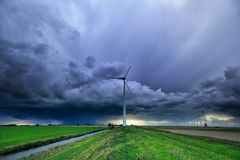 Stormy rainy sky over countryside with wind turbines stock image